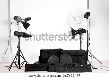Empty photo studio with lighting equipment,  bags and backdrop - stock photo