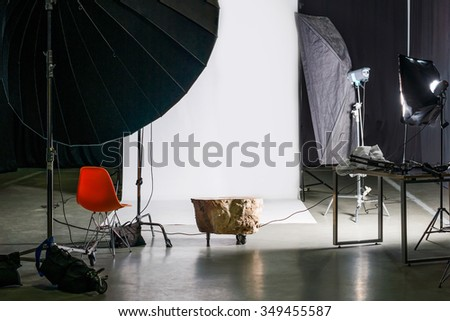 Empty photo studio with modern interior and lighting equipment. Preparation for studio shooting: empty chair and studio lighting - stock photo