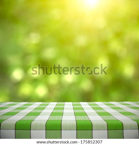 Empty picnic table on green foliage bokeh background - stock photo