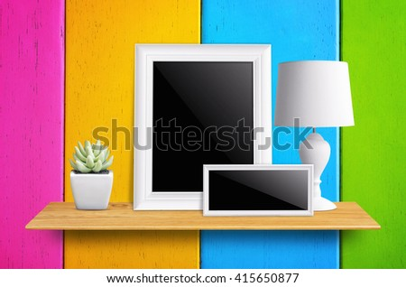 Empty picture frame isolated with clipping path, lamps and potted cactus on bookshelf  - For product display. - stock photo