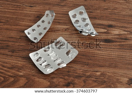 Empty pill blisters pack on a wooden background. Drug prescription for treatment medication. Pharmaceutical medicament, cure in container for health. Antibiotic, painkiller - stock photo