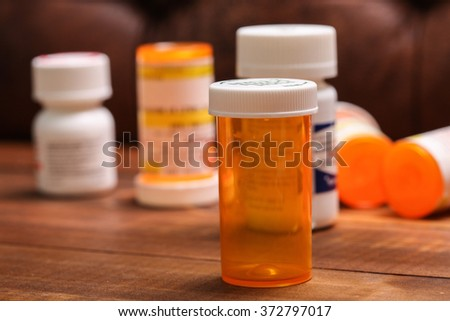 Empty pills bottle on wooden table - stock photo