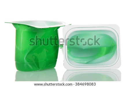 Empty plastic cups with yogurt close up isolated on white background. - stock photo