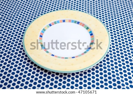 Empty plat on table caver by blue tablecloth - stock photo