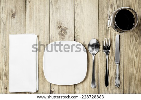 Empty plate, a napkin dining room, cutlery set and wine glass on a wooden background - stock photo