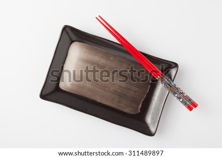Empty plate and chopsticks on white background - stock photo
