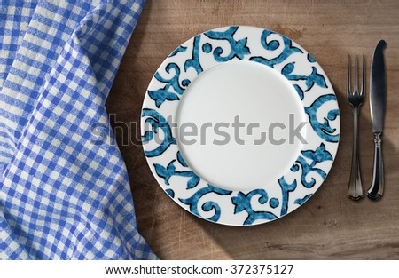 Empty Plate and Cutlery - Table and Tablecloth / Empty white and blue plate on a wooden table with silver cutlery, fork and knife, and a blue and white checkered tablecloth  - stock photo
