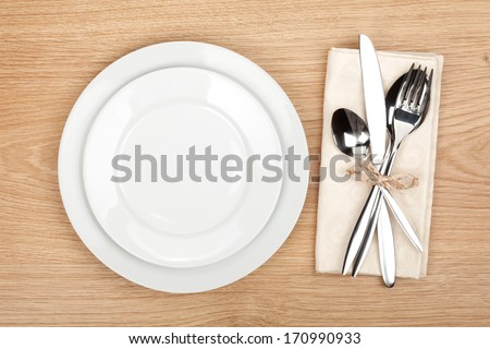 Empty plate and silverware set on wooden table - stock photo
