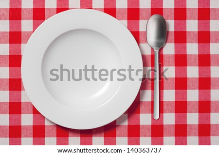 empty plate and spoon on red and white checkered tablecloth  - stock photo