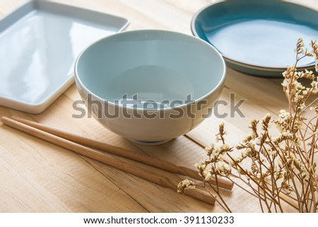 Empty plate and sushi chopsticks on wood table - stock photo