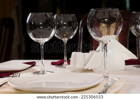 Empty plate and wineglasses on a formal dinner table in a restaurant, low angle view - stock photo