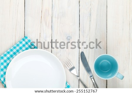 Empty plate, cup and silverware over white wooden table background. View from above with copy space - stock photo