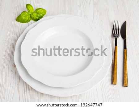 empty plate, cutlery set, mint leaf - stock photo