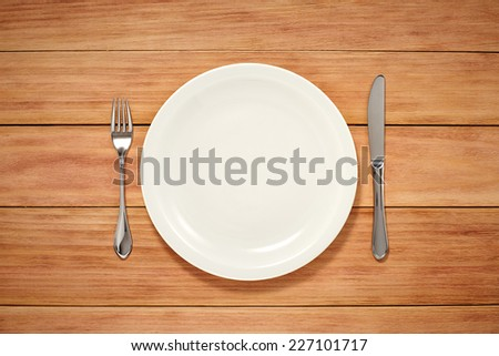 Empty Plate, Fork and Knife on wooden background. Top View with Text Space - stock photo