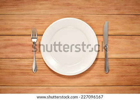 Empty Plate, Knife and Fork on wooden background. Top View Text Space - stock photo