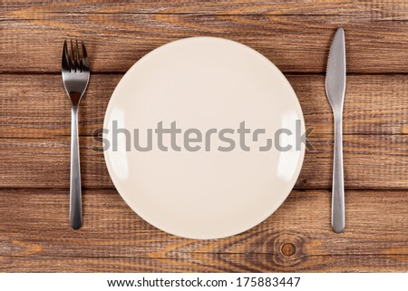 Empty plate on a wooden table - stock photo