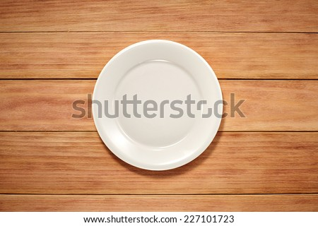 Empty Plate on wooden background. Top View with Text Space - stock photo