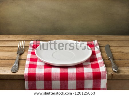 Empty plate on wooden table over grunge background - stock photo