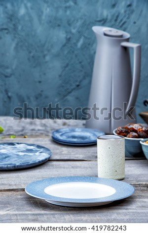 Empty plate, rustic drinking cup, thermos, on wooden table on a light blue stone background. Tableware set. Dishes for a meal. Empty template to put your food on the plate. picnic - stock photo