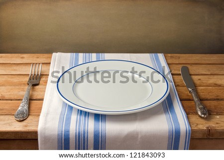 Empty plate with fork and knife on tablecloth on wooden table over grunge background - stock photo