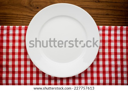 Empty plate with fork and knife on tablecloth over wooden background - stock photo