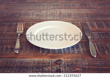 Empty plate with knife and fork on vintage wooden table - stock photo