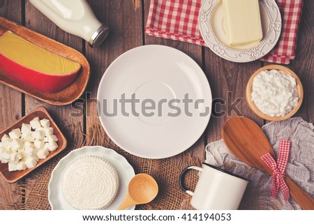Empty plate with milk, cheese and butter on wooden background. View from above. Flat lay - stock photo