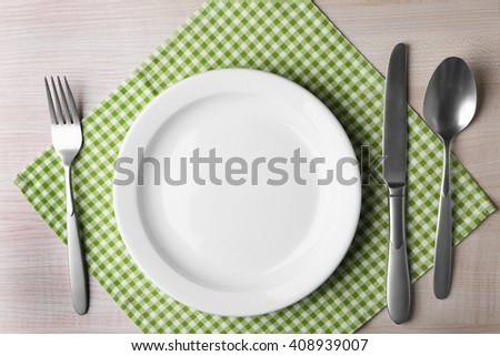 Empty plate with silver cutlery and napkin on wooden table, top view - stock photo