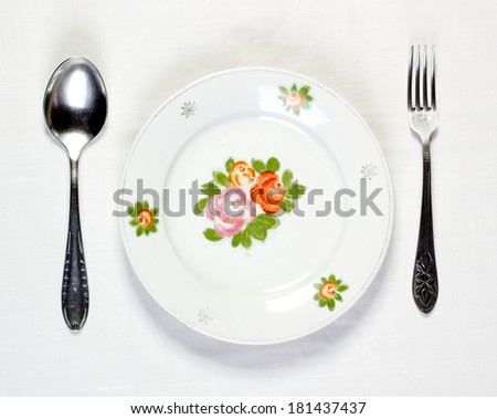 Empty plate with spoon and fork - stock photo