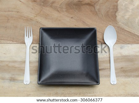 empty plate with spoon and fork ,top view. on wood background - stock photo