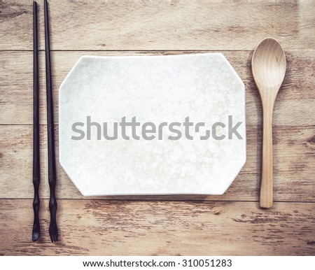 Empty plate with wooden Spoon and chopsticks on wooden table - stock photo