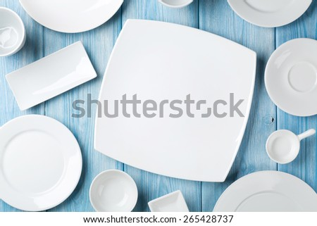 Empty plates and bowls on blue wooden background. Top view with copy space - stock photo