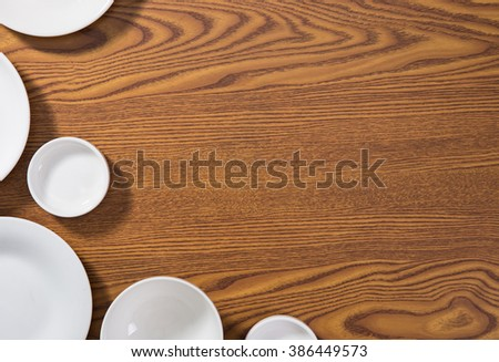 Empty plates and bowls on wooden background. - stock photo