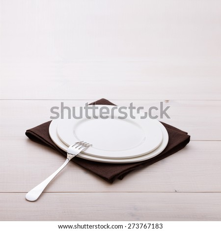 Empty plates and cutlery on table cloth on white wooden table for dinner. Square - stock photo