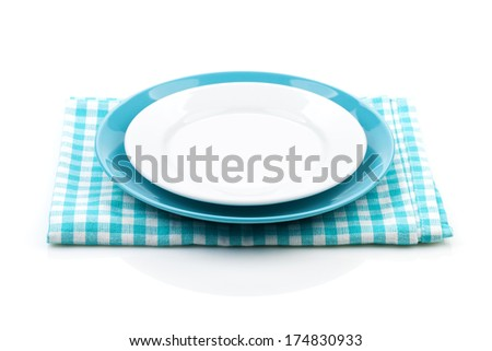 Empty plates over kitchen towel. Isolated on white background - stock photo