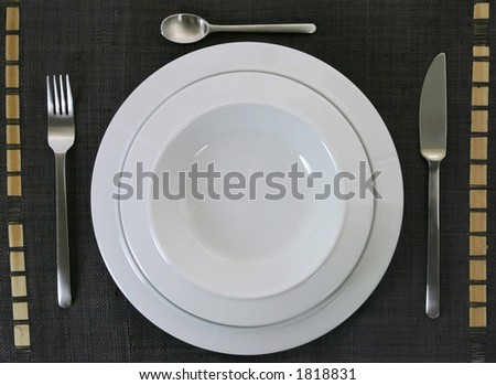Empty porcelain plates with knife, fork and teaspoon on a brown ethnic handcrafted cloth - stock photo