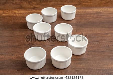 Empty porcelain ramekin set on wooden table - stock photo