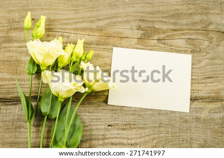 Empty postcard and colorful flowers on wooden background - stock photo