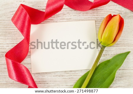 Empty postcard with colorful flower and red ribbon on wooden background - stock photo