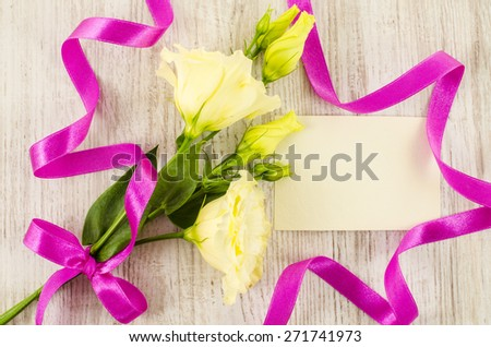 Empty postcard with flower and pink ribbon on wooden background - stock photo
