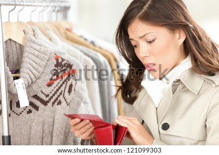 Empty purse or wallet - no money for shopping concept. Woman shopping for clothing in clothes store. - stock photo