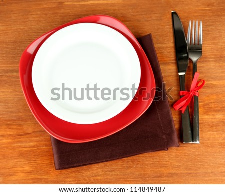 Empty red and white plates with fork and knife on wooden table, close-up - stock photo