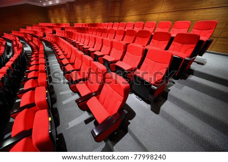 Empty red arm-chairs stand rows in hall - stock photo