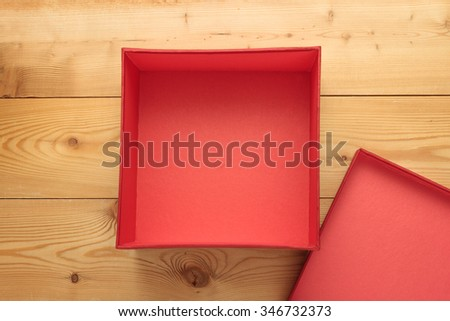 Empty red box on a wooden background - stock photo