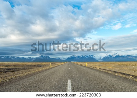 Empty road leading to Skaftafelt mountains, Iceland. - stock photo