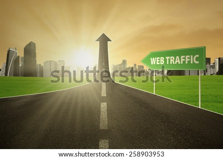 Empty road turning into arrow upward with web traffic text on the signboard, symbolizing web activity is growing - stock photo