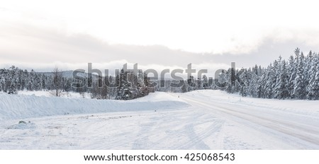Empty road with huge snow banks on sides on cloudy winter day - stock photo