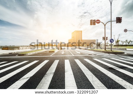 empty road with zebra crossing and direction board in modern city under sunlight - stock photo