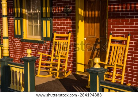 Empty rocking chairs on porch of red brick country home. - stock photo