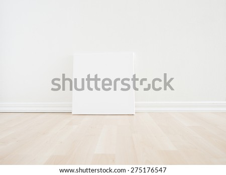 Empty room interior with blank artwork picture frame standing on wooden floor. Bright white scandinavian design and clean contemporary architecture. The room works as backdrop for a new home.  - stock photo